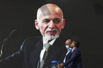 Passengers pass a mural of Afghan president Ashraf Ghani at Hamid Kazrai Airport in Kabul. Ghani fled the capital as the Taliban moved in.