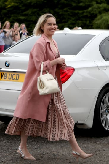 Coat check ... 'Game of Thrones' actress Emilia Clarke arrives at the wedding of Kit Harington and Rose Leslie.