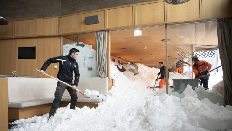 People clear snow from inside the Hotel Saentis in Schwaegalp, Switzerland, on Friday.