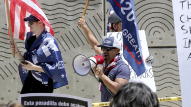 Three Trump supporters hold flags and yell at people while being kept apart by the LAPD at the 'Families Belong Together: Freedom for Immigrants' march on Saturday.