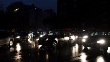 Cars drive through an unlit street during a blackout in Buenos Aires.