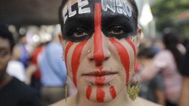 "A woman poses for a photo with the words ""Not him"" written in Portuguese on her face during a protest against Jair Bolsonaro, a far-right presidential candidate in Sao Paulo."