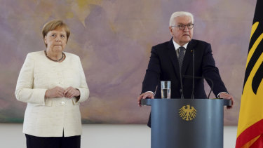 German Chancellor Angela Merkel, left, steadies her hands on Thursday.