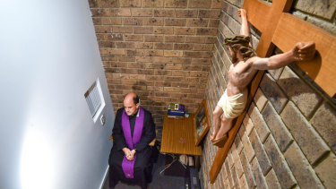 Father Nicholas Pearce in the confessional atHoly Family Church in  MountWaverley.