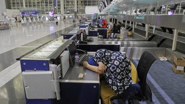 Stranded travelers sleep at the check-in counters at the Hong Kong International Airport.
