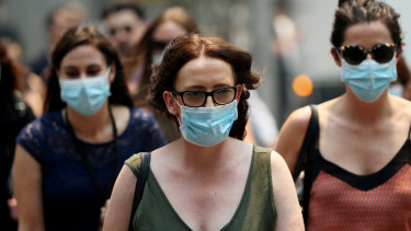 People are seen wearing face masks to protect from smoke haze as they cross a busy city street on December 05, 2019 in Sydney, Australia. Smoke haze continues to hang over the city as more than 50 bushfires continue to burn across New South Wales.