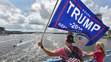 Brian Masotti, left, and Tracey Warren wave flags at the hundreds of boats idling on the St. Johns River during a rally in Jacksonville, Fla., celebrating President Donald Trump's birthday.