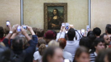 Visitors crowd in front of Leonardo da Vinci's painting Mona Lisa at The Louvre in Paris.