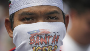 A protester covering his face takes a part in a rally to celebrate the government's move to withdraw plans to ratify a UN anti-discrimination convention  in Kuala Lumpur on Saturday.