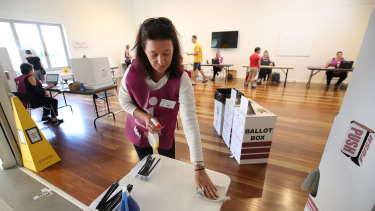 An election official sanitises a polling booth during the Brisbane council election in March.