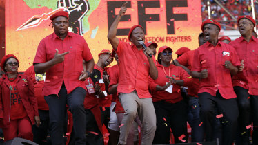 Leader of the Economic Freedom Fighters (EFF) party, Julius Malema, centre, sings and dances with party members at an election rally in Soweto, South Africa.
