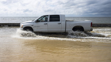 A truck drives through seawater as Beach Boulevard floods in Waveland, Mississippi.