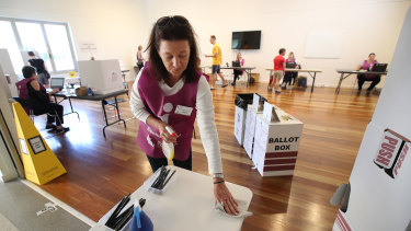 Voting during COVID-19: An election official sanitises a polling booth during the Brisbane council election in March.
