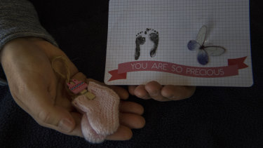 Ali holds mementos of her daughter who had developed severe abnormalities in utero.