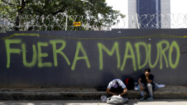 "A man reaches into his bag to retrieve some food waste that was given to him by a Chinese restaurant as he sits in front of security fence spray-painted with a message that reads in Spanish: ""Maduro out,"" in Caracas, Venezuela."