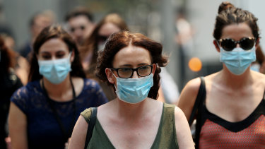 People are seen wearing face masks to protect from smoke haze as they cross a busy city street on December 5, 2019 in Sydney.