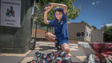 Eco-detective at Garran Primary Rex Martin, 10, crushes collected cans as part of the school's extensive recycling program.