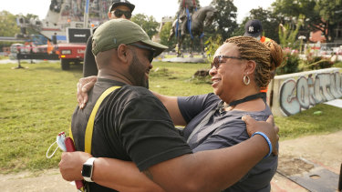 Devon Henry, owner of the construction company that removed the statue, hugs his mother, Freda Thornton, after the removal of the statue from Monument Avenue, Richmond, Virginia.
