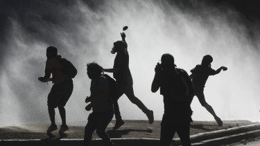 Anti-government demonstrators throw rocks at a police water canon trying to disperse them in Santiago, Chile, last week.