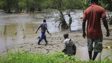 Residents gather after flooding on the the River Hululu, which joins the Rver Lubiriha, near Beni, eastern Congo.