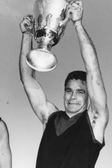 Ron Barassi holds the 1964 premiership cup aloft after the Demons triumph over Collingwood.
