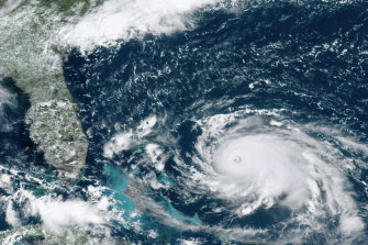 A satellite image of Hurricane Dorian as it bore down on the Bahamas on Saturday, local time. New projections show it is likely to curve upward enough to potentially spare Florida a direct hit.