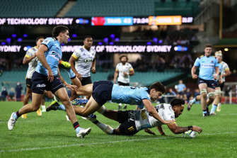 Hurricanes player Pepesana Patafilo barges over against the Waratahs.