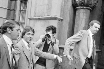 Christopher Dale Flannery (second from left) is led handcuffed into Melbourne's City Watch House in October 1981 to be charged with the murder of Roger Wilson.