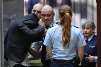 Meth Mean covers his head as he arrives at court on Friday.