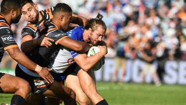 Kieran Foran busts through the Tigers line to almost score a try.