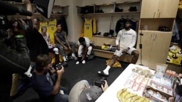 LeBron James sits in the Lakers' locker room with the press before the NBA pre-season game against Denver.