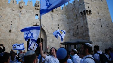 Israelis wave national flags outside the Old City's Damascus Gate in Jerusalem on Sunday.