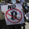 Farmers hold signs emblazoned with messages against the country adopting bitcoin as legal tender in San Vicente, El Salvador.