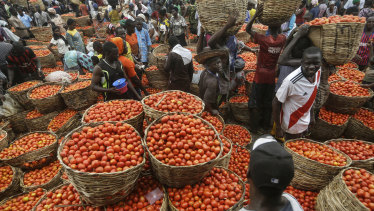 People buy tomatoes from a vegetable market in the commercial capital Lagos, Nigeria.