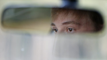Charlie Shebes, 16, a junior at Marjory Stoneman Douglas High School, is reflected in his rear view mirror as he drives to school.