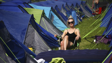 A festivalgoer sits in the sunshine amongst tents at the Glastonbury Festival in England on Friday.