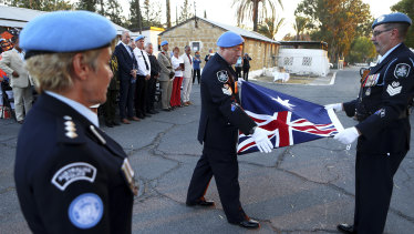 Australian U.N police officer fold the Australian flag during a flag-lowering ceremony to ended Australia's peacekeeping contribution in Cyprus in Nicosia in 2017.