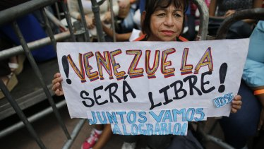 """A supporter of opposition leader and self-proclaimed interim president of Venezuela Juan Guaido, holds a sign that reads in Spanish """"Venezuela will be free! We will do it together."""""""