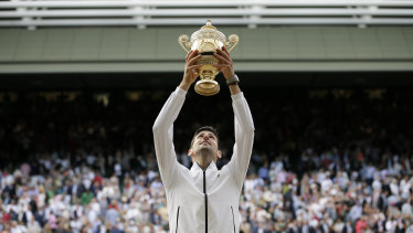 Novak Djokovic lifts the trophy after defeating Switzerland's Roger Federer at Wimbledon in 2019