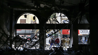 Lebanese army soldiers and people gather near a branch of the Libano Francaise Bank that was set on fire by anti-government protesters during confrontations that began on Monday night in the northern city of Tripoli, Lebanon.