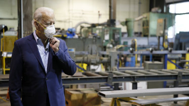 Democratic presidential candidate Joe Biden adjusts his mask during a tour of McGregor Industries, a metal fabricating facility