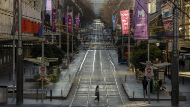 A lone pedestrian crosses an empty Bourke Street in Melbourne's CBD on Sunday morning.