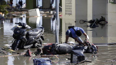 An Indonesian man tries to get his motorbike upright at a tsunami devastated area in Talise beach, Palu.