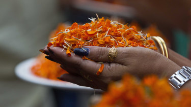 A Bharatiya Janata Party supporter holds marigold flower petals and celebrates at the party head office in Gauhati, India.