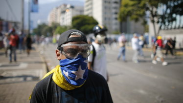 An anti-government protester, masked with a Venezuelan flag, looks toward security forces during clashes near La Carlota airbase in Caracas, Venezuela.