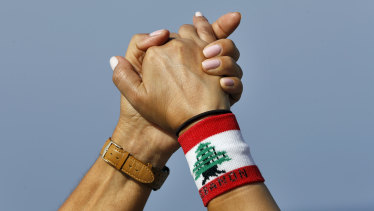 Thousands of Lebanese have formed a human chain along highways and coastal roads to link Beirut and other cities in a show of solidarity with the anti-government protests.