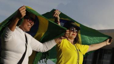 Supporters of Brazil's President Jair Bolsonaro hold Brazilian national flags outside the Supreme Court on Thursday.