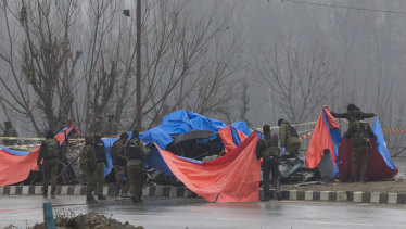 Indian policemen cover the wreckage of a bus with plastic sheets at the site of the explosion in Pampore, Indian-controlled Kashmir on February 15.