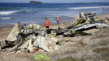 Workers inspect the remains of shipping containers washed up on Birdie Beach, NSW.