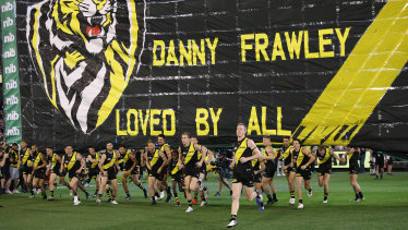 In memory: Richmond players run through the banner dedicated to AFL great Danny Frawley.